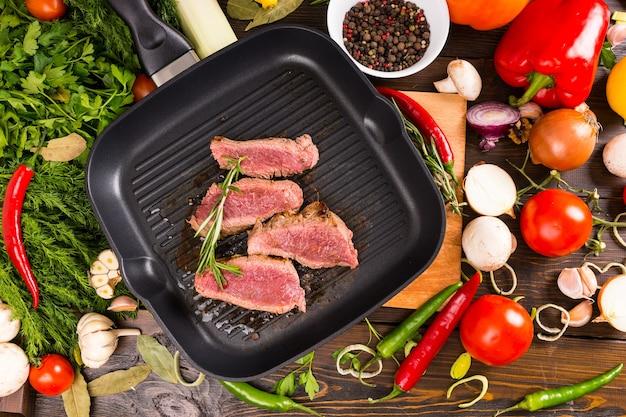 Высокий угол обзора редких приправленных нарезок говядины, шипящих в горячей сковороде, в окружении множества ингредиентов - ярких овощей, свежих трав и специй