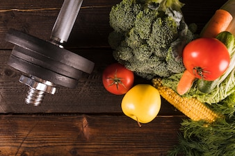 High angle view of raw vegetables and dumbbells on wooden background