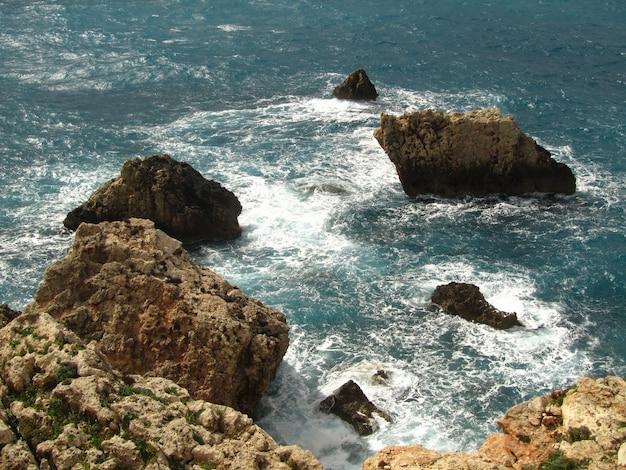 マルタの昼間の日光の下で波状の海に囲まれた岩の高角度のビュー