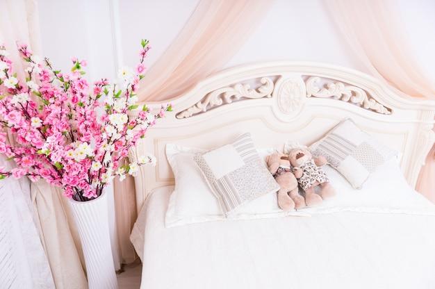 Романтический розово-белый букет цветов под высоким углом у кровати с парами плюшевых мишек мужского и женского пола, прижимающимися друг к другу