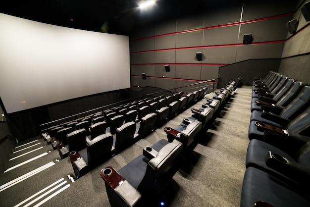 Высокий угол обзора экрана и ряды удобных красных стульев в кинотеатре с красной подсветкой