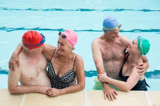 수영장에서 즐기는 노인 커플의 높은 각도보기