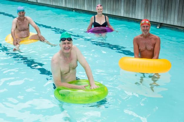 수영장에서 풍선 고리와 함께 수영하는 노인의 높은 각도보기