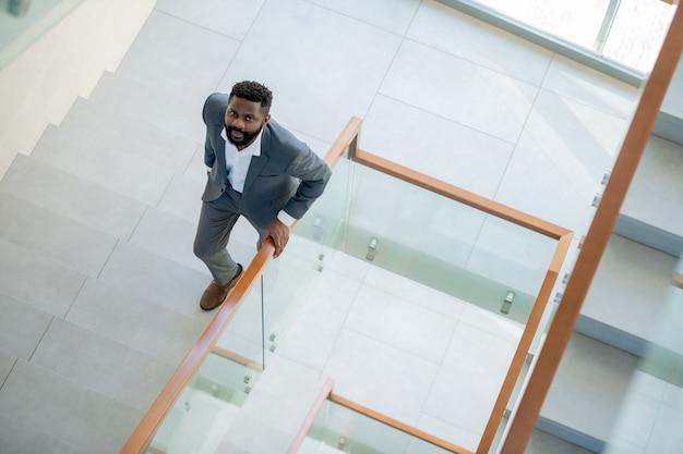 階段を上って見ているスーツを着た深刻なアフリカ系アメリカ人のひげを生やしたビジネスマンの高角度ビュー