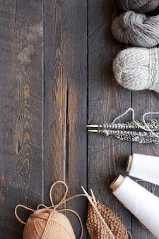木製テーブルの縫製と編み物の糸と羊毛の糸と編み針の高角度ビュー