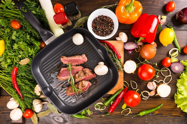 Высокий угол обзора нарезанного редкого ростбифа, шипящего на раскаленной чугунной сковороде, в окружении свежих ингредиентов