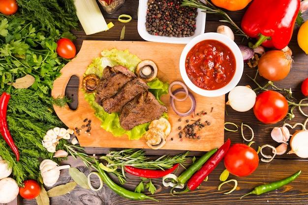 Высокий угол обзора небольших кусочков говядины, лежащих на деревянной разделочной доске с соусом из сальсы в окружении множества свежих разноцветных овощей, трав и специй