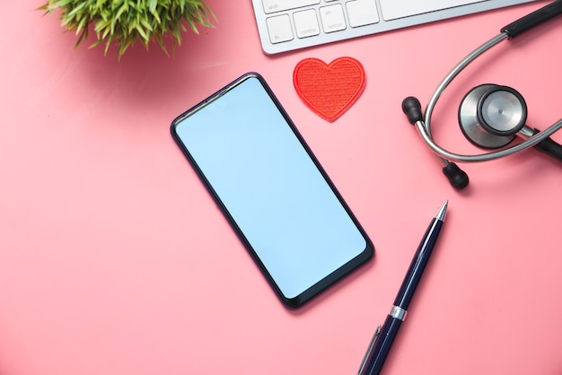 Высокий угол обзора смартфона, клавиатуры и стетоскопа на розовом фоне.