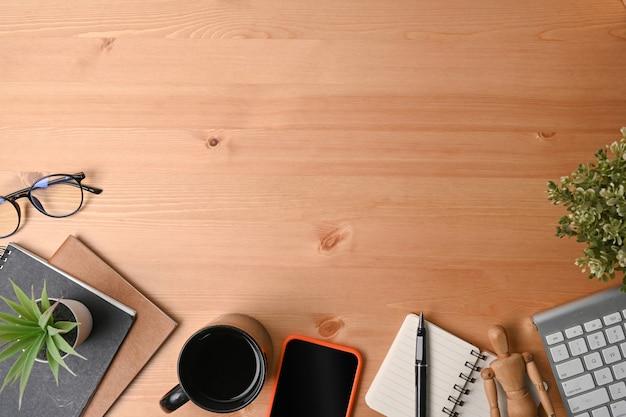 Высокий угол обзора смартфона, ноутбука, очков и кофейной чашки на деревянном столе.