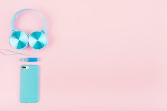 High angle view of smartphone and headphone on pink backdrop