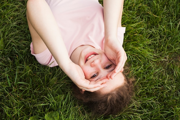 草の上に横たわると彼女の目をシールド笑顔の女の子の高角度のビュー