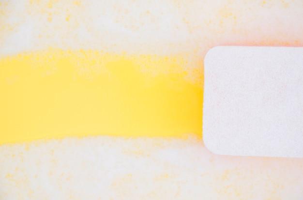 노란색 배경에 스폰지 청소 비누 비눗물의 높은 각도보기