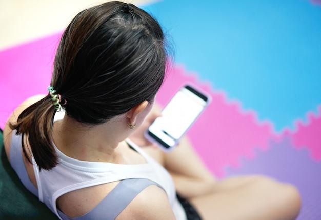 스포츠웨어 여성의 높은 각도 보기는 복사 공간이 있는 집 실내 운동 에어로빅 후 앉아서 스마트폰을 사용합니다.