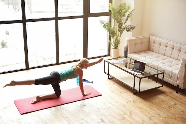 Высокий угол обзора спортивной зрелой блондинки в спортивной одежде, тренирующейся дома перед