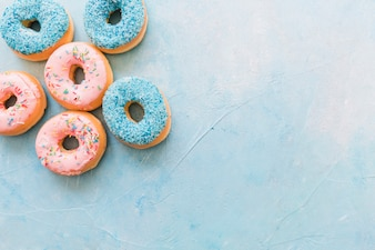 High angle view of tasty donuts on blue background