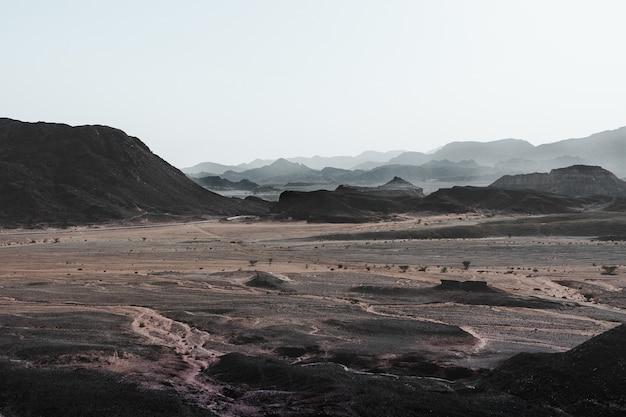 丘や山々に囲まれた壮大な砂漠のハイアングルビュー