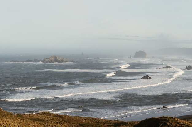 Высокий угол обзора волнистого моря, окруженного скалами, покрытыми туманом в дневное время