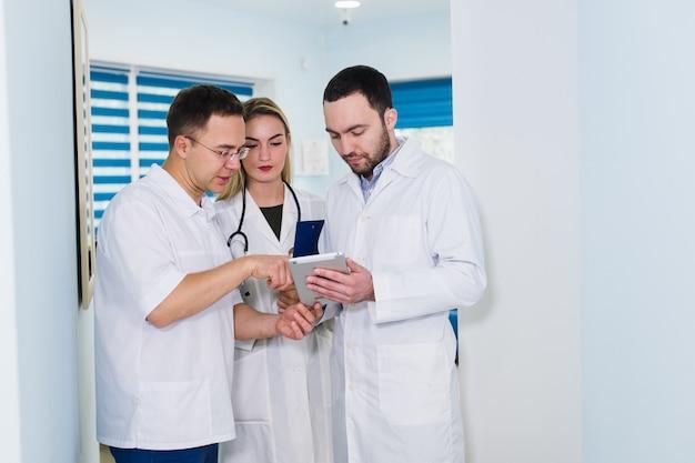 病院ホールで会話をしている白衣の3人の医師の高角度のビュー