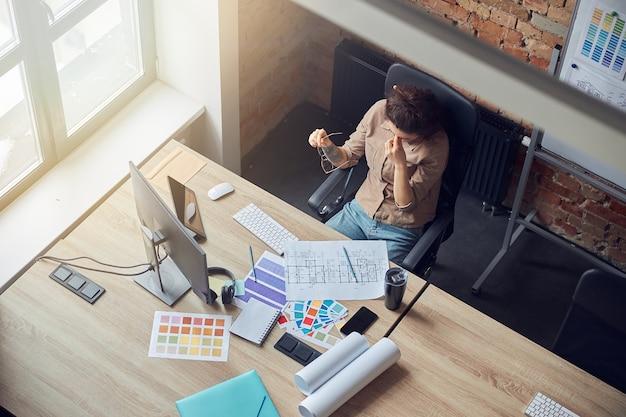 작업하는 동안 안경을 벗고 휴식하는 피곤한 인테리어 디자이너 여성의 높은 각도 보기