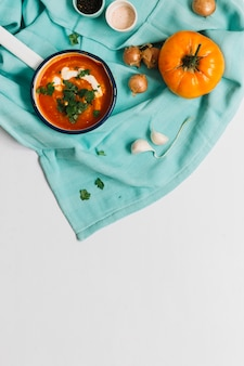 High angle view of tomato soup with garlic and onion on white backdrop