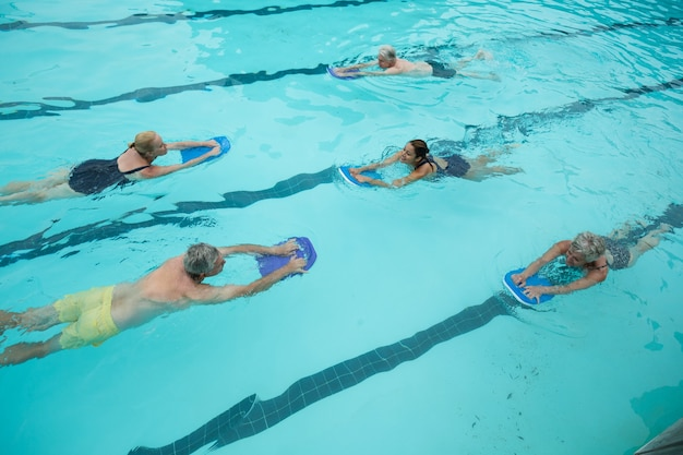 수영장에서 수영하는 수석 수영과 트레이너의 높은 각도보기