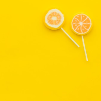High angle view of two citrus lollipops on yellow backdrop