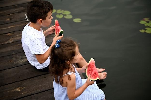 スイカのスライスを手に、足を水に下げて桟橋に座って、田舎で夏の夜を楽しんでいる、男の子と女の子の2人のかわいい子供たちのハイアングルビュー。