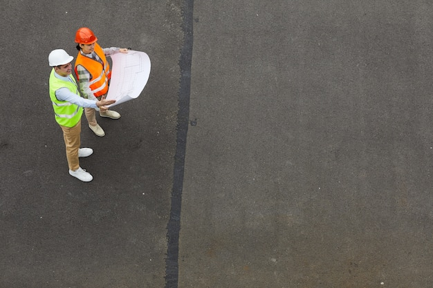 屋外に立って新しいプロジェクトの青写真を調べている2人のエンジニアのハイアングルビュー