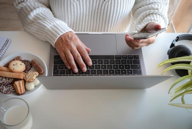 ラップトップで作業している2つの女性の手の高角度ビュー。手に携帯電話。白い机