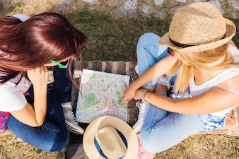 High angle view of two female hikers looking for direction in map