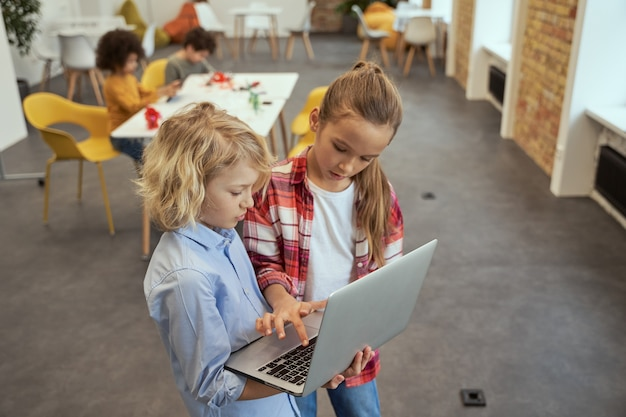 두 명의 사랑스러운 어린 소년과 소녀가 노트북을 들고 서 있는 것을 높은 각도로 볼 수 있습니다.