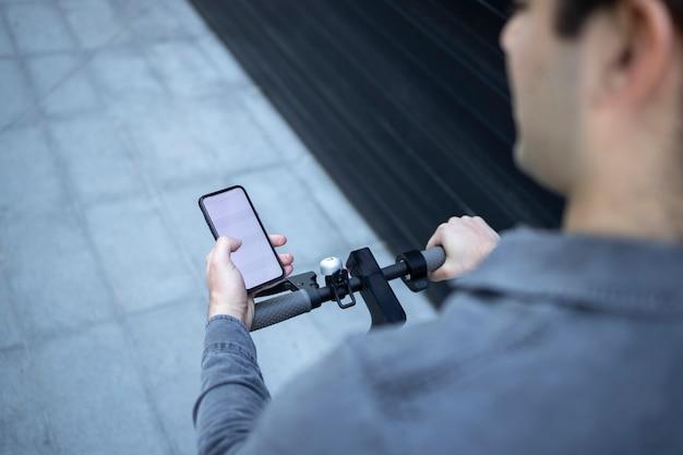 電動スクーターに乗っているときに彼のスマートフォンでアプリを使用している認識できないビジネスパーソンの高角度ビュー。