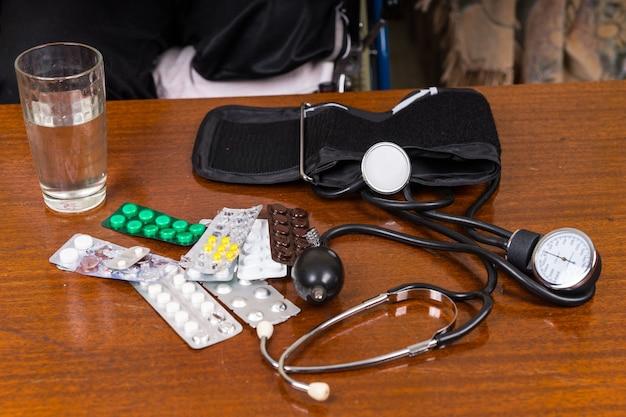 Высокий угол обзора различных домашних медицинских принадлежностей для измерения артериального давления на столе - стакана воды, различных таблеток в блистерных упаковках из фольги, стетоскопа и манжеты для измерения артериального давления с манометром