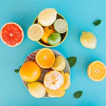 High angle view of various citrus fruits on blue backdrop