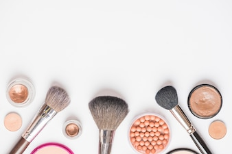 High angle view of various cosmetic products on white backdrop