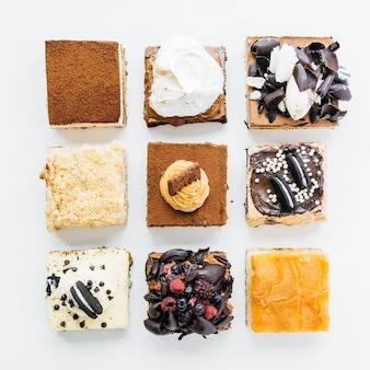 High angle view of various delicious pastries on white background