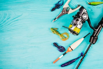 High angle view of various fishing equipments on turquoise background