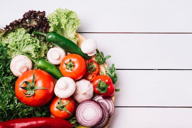 Взгляд высокого угла различных свежих овощей на деревянном столе