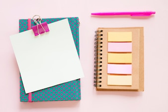 High angle view of various stationeries on pink background