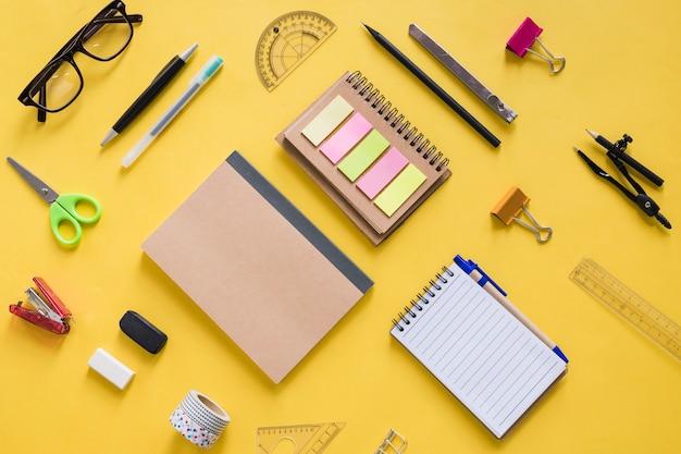 黄色の表面上の様々な文房具の高い角度のビュー