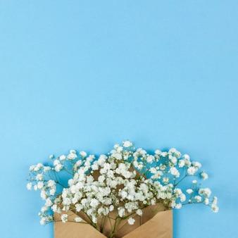 파란색 배경에 갈색 봉투와 하얀 아기의 숨 꽃의 높은 각도보기