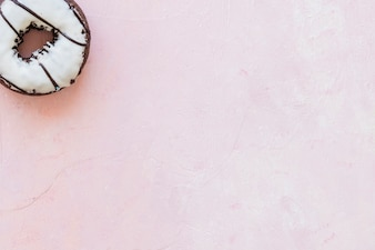 High angle view of white chocolate donut on pink background