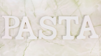 High angle view of white pasta word on marble