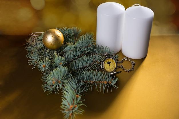 エバーグリーンブランチ、ゴールドボール、コピースペースとスポット照明付きのアンティーク懐中時計と黄金色の背景に白い柱のキャンドルの高角度ビュー