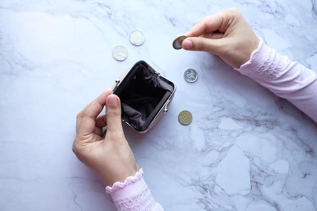 財布にコインを手で節約する女性の高角度ビュー