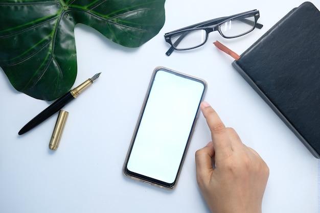 Высокий угол обзора руки женщины, использующей смартфон
