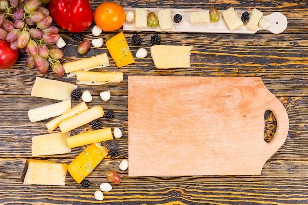 木目とコピースペースのある素朴な木製のテーブルで、さまざまなグルメチーズと新鮮な果物に囲まれた木の板の高角度ビュー
