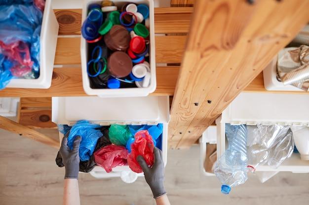 家庭でのごみの分別、保管、リサイクルのコンセプトのためのプラスチック製のゴミ箱を備えた木製の棚ラックの高角度ビュー
