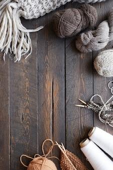 Высокий угол обзора деревянного стола с клубками пряжи и готовой шерстяной одежды на нем
