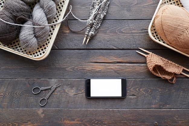 Высокий угол обзора деревянного стола с корзиной с клубками шерсти и мобильного телефона на нем